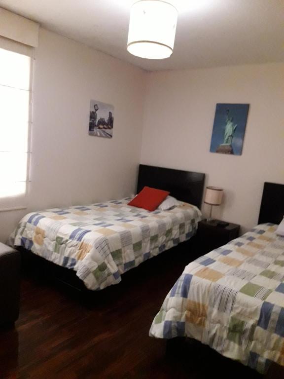 A bed or beds in a room at Apartamentos Amoblados de 1 Y 2 dormitorios