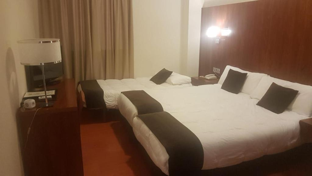 A bed or beds in a room at Sercotel Familia Conde