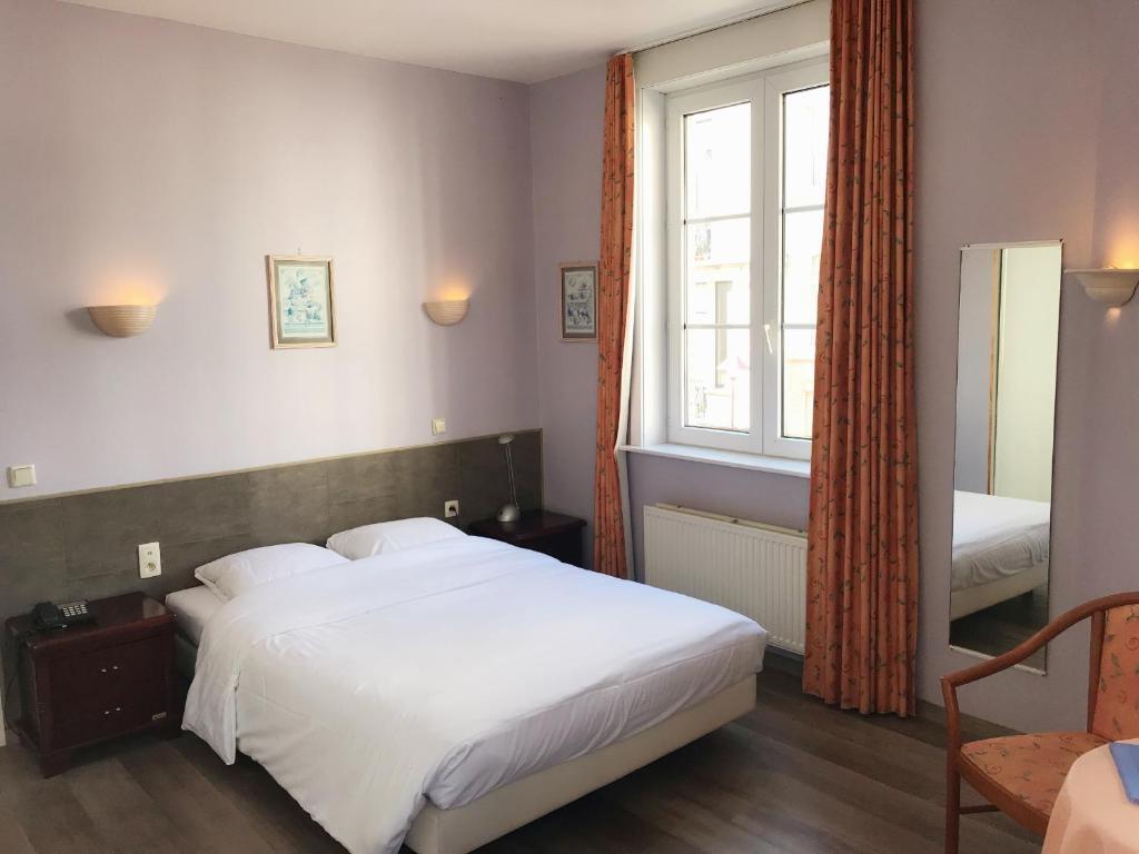 Ein Bett oder Betten in einem Zimmer der Unterkunft Hotel Claridge