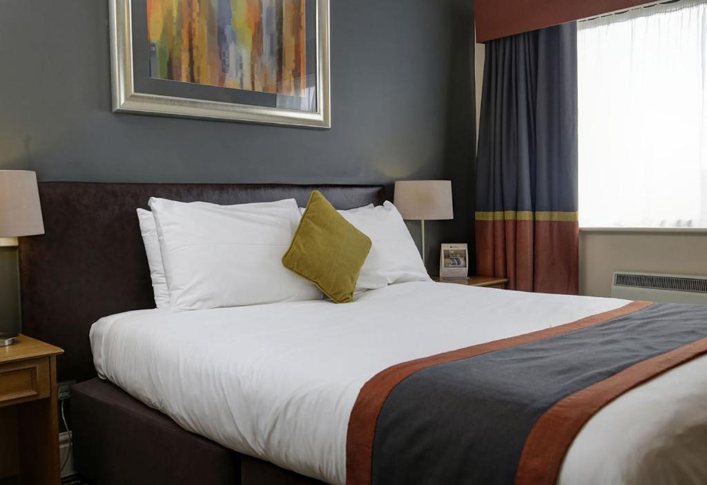 A bed or beds in a room at The Broughton Hotel by Greene King Inns