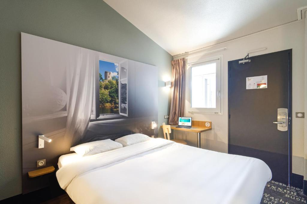 A bed or beds in a room at B&B Hôtel CHATEAUROUX Aéroport