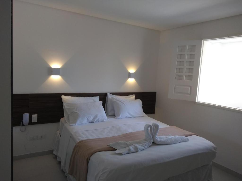 A bed or beds in a room at Pousada Galemares