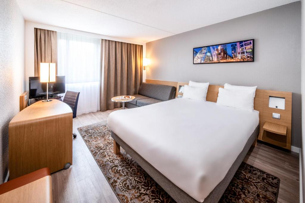 A bed or beds in a room at Novotel Eindhoven