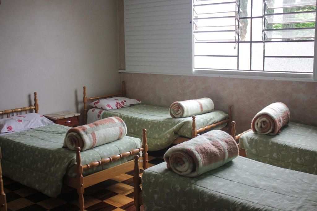 A bed or beds in a room at Pousada Irmãs Franciscanas