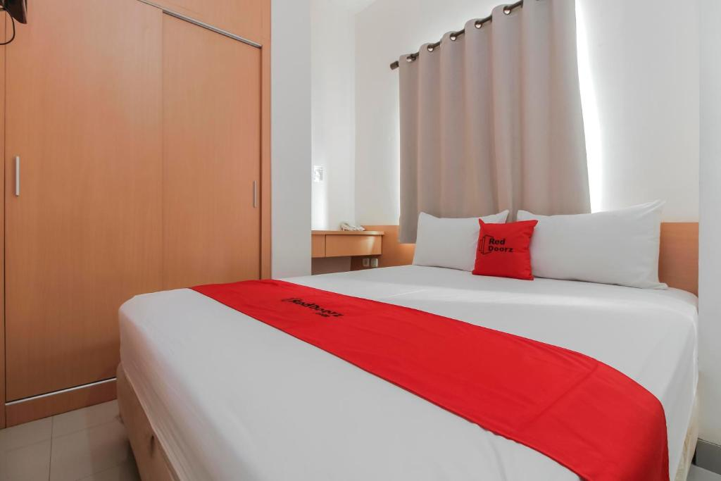 A bed or beds in a room at RedDoorz Plus near Galaxy Bekasi