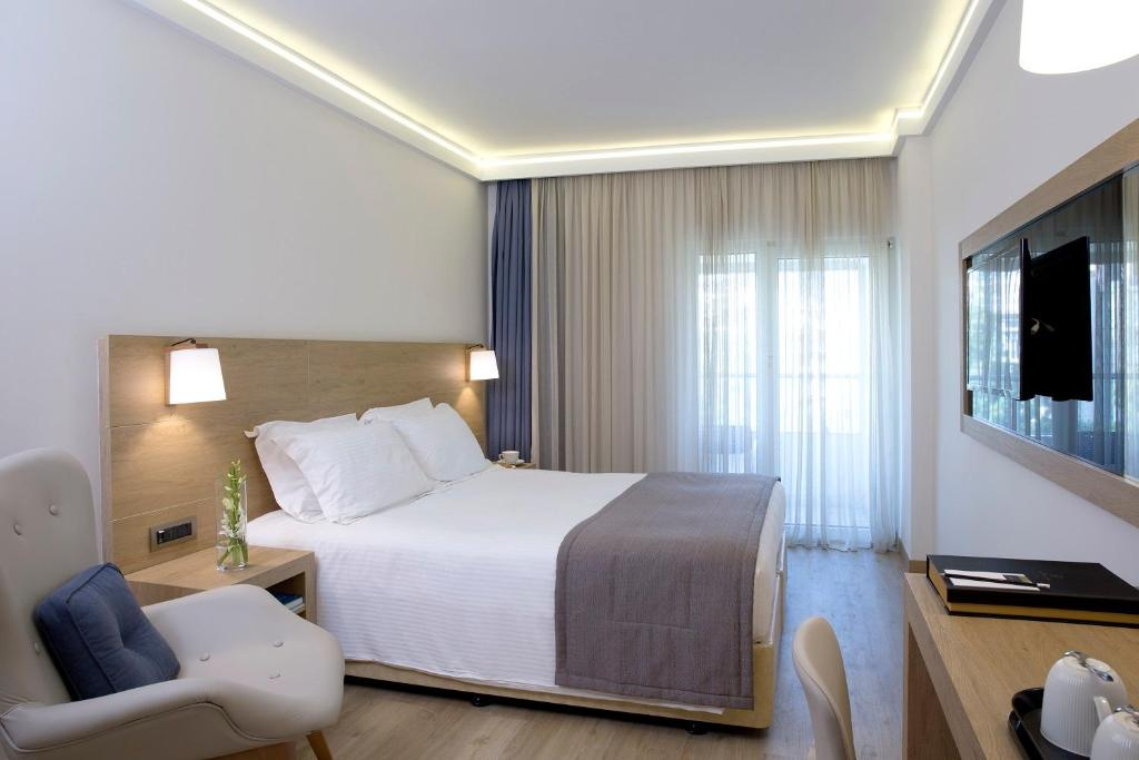 A bed or beds in a room at Golden Age Athens Hotel