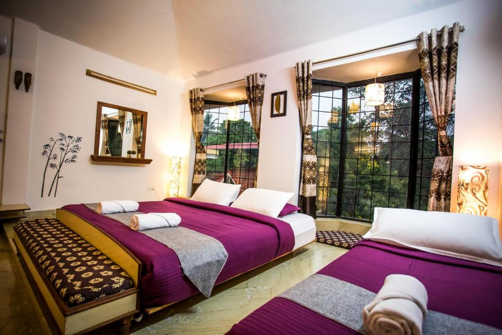 A bed or beds in a room at Siolim Holiday Apartments