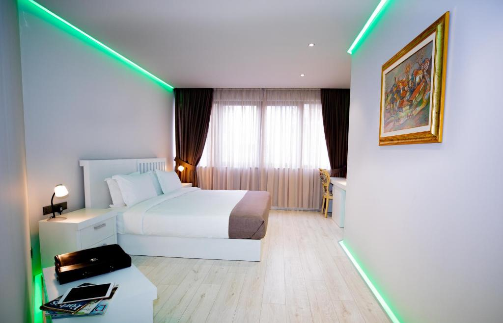 A bed or beds in a room at Metro Hotel Tirana