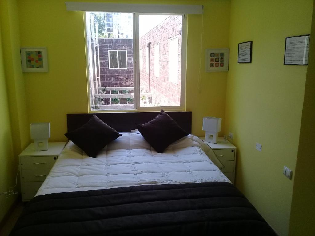 A bed or beds in a room at Hotel Barrio Yungay
