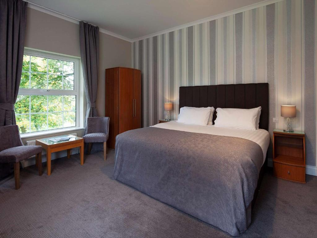 A bed or beds in a room at Elfordleigh Hotel