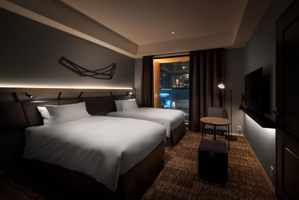 A bed or beds in a room at Nest Hotel Osaka Umeda