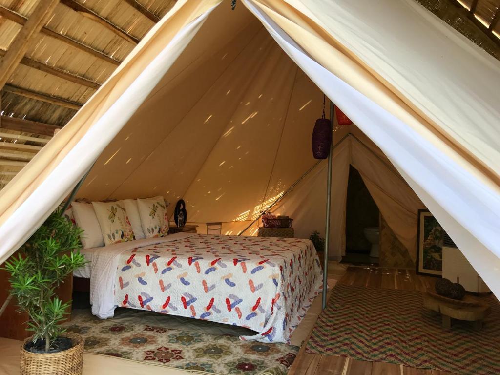 A bed or beds in a room at Tangkoy Eco Glamping & Villas El Nido