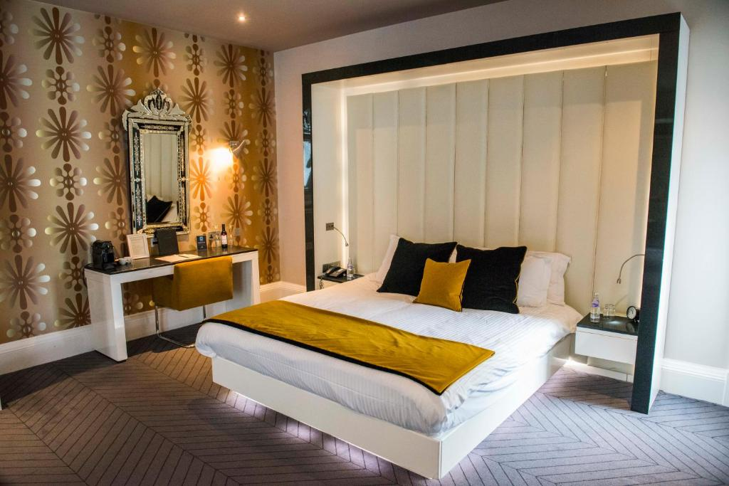 A bed or beds in a room at The Rutland Hotel & Apartments