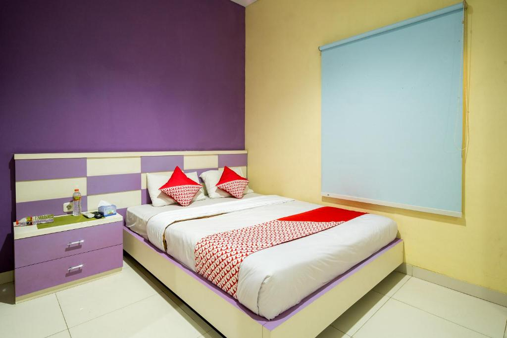 A bed or beds in a room at OYO 342 De'kayakini Hotel