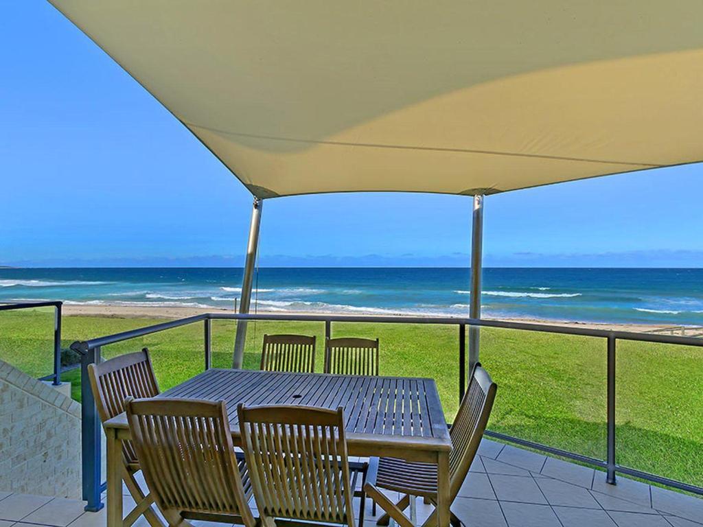 A balcony or terrace at Beachfront Luxury