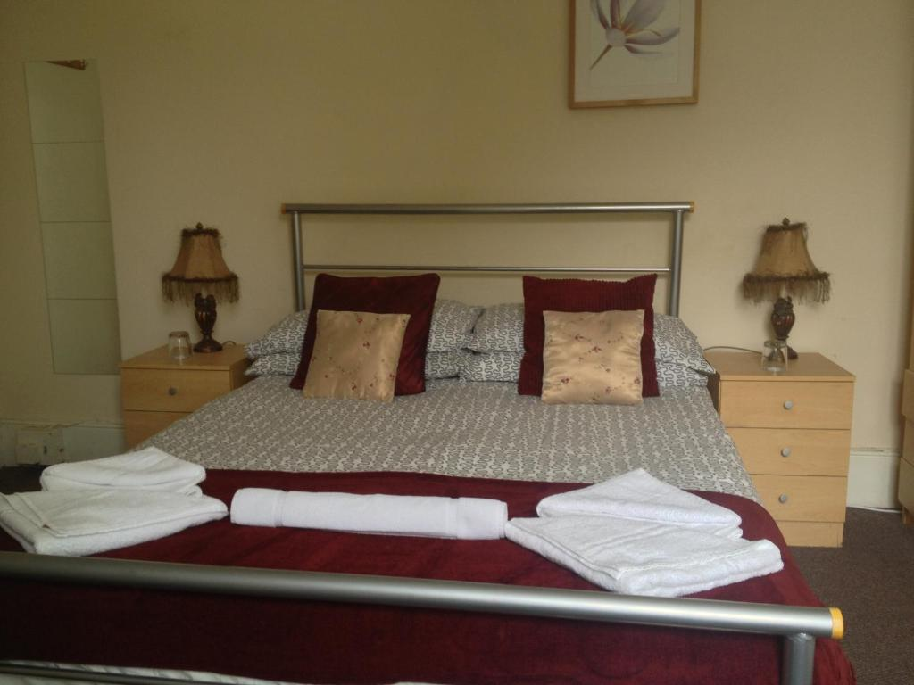A bed or beds in a room at Malvern Lodge Guest House