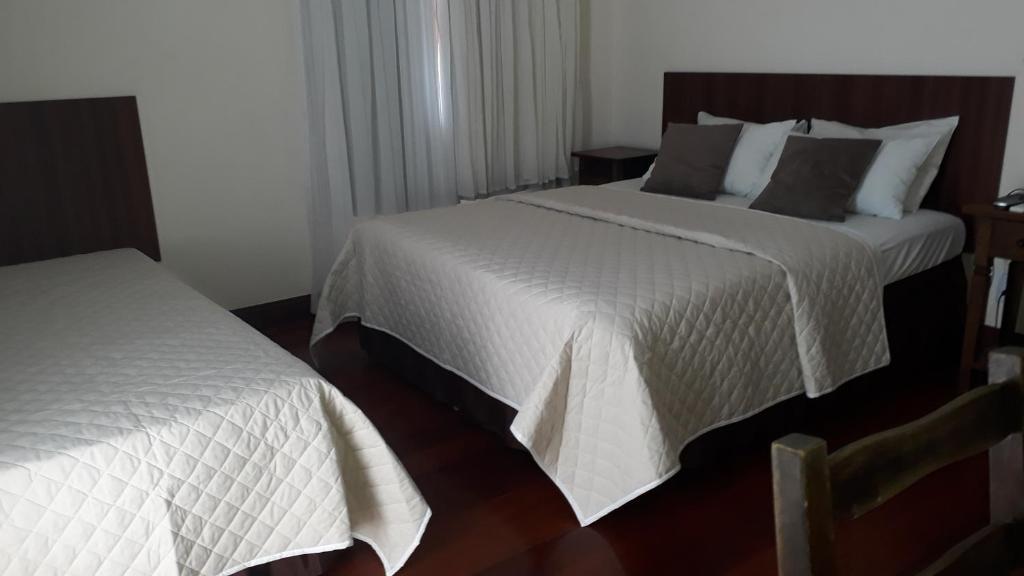 A bed or beds in a room at Pousada Pau de Canela