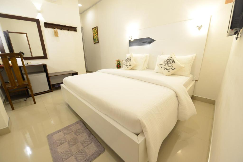 A bed or beds in a room at Diva Villa Airport Transit Hotel