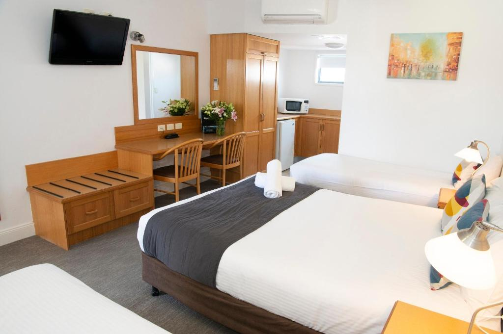 A bed or beds in a room at Rockpool Motor Inn