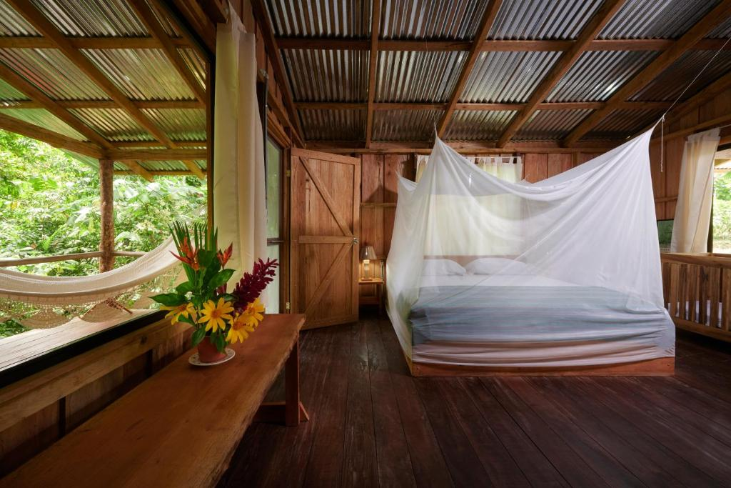 A bed or beds in a room at Finca Amistad Cacao Lodge
