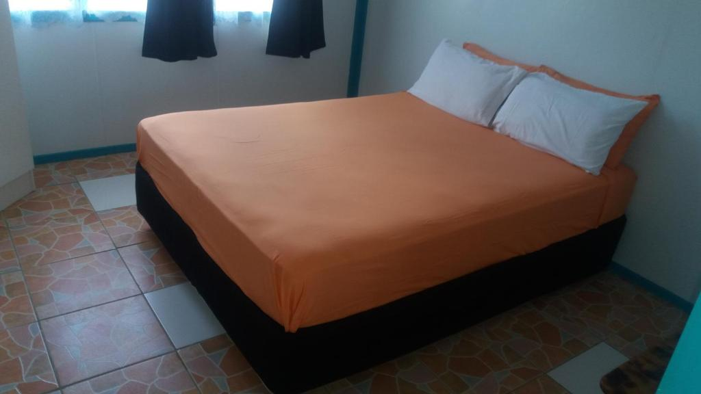 A bed or beds in a room at Aitutaki Budget Accommodation