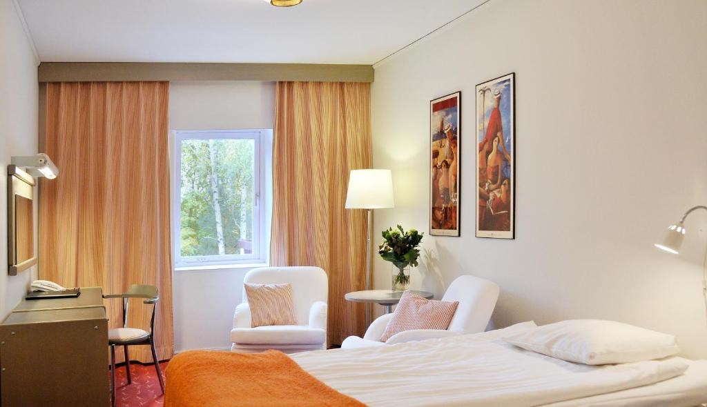 A bed or beds in a room at Ariston Hotell