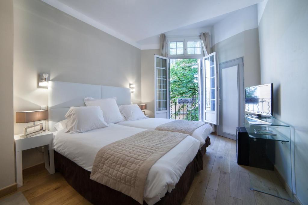 A bed or beds in a room at Hôtel de France