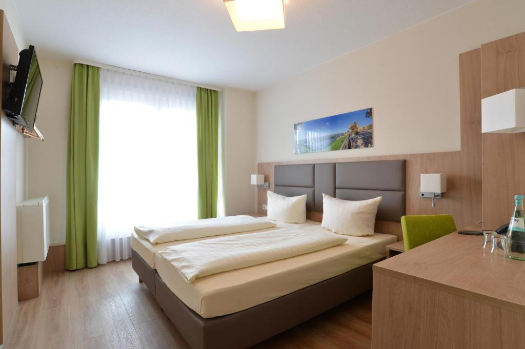 A bed or beds in a room at City-Hotel Kurfürst Balduin