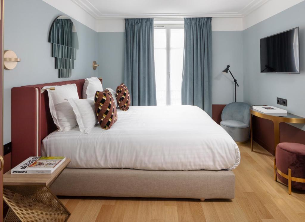 A bed or beds in a room at Hôtel Parisianer