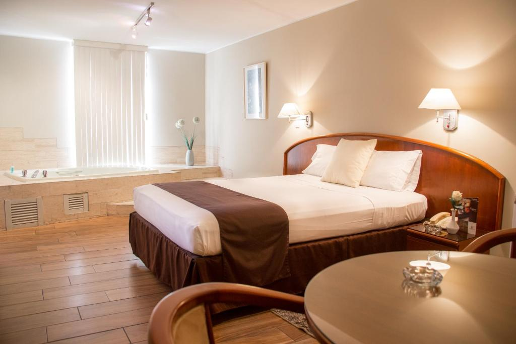 A bed or beds in a room at Hotel Park Suites