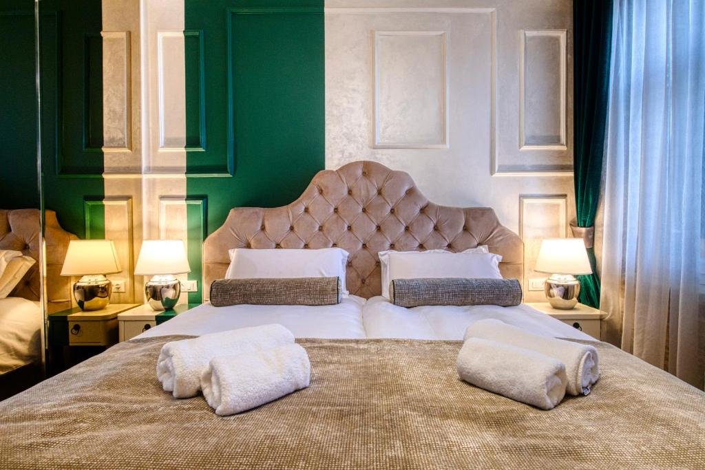 A bed or beds in a room at Riva Palace - design rooms