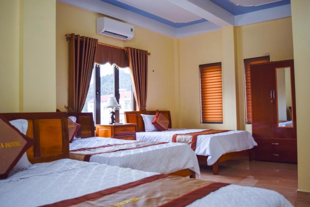 A bed or beds in a room at Phong Nha Orient Hotel