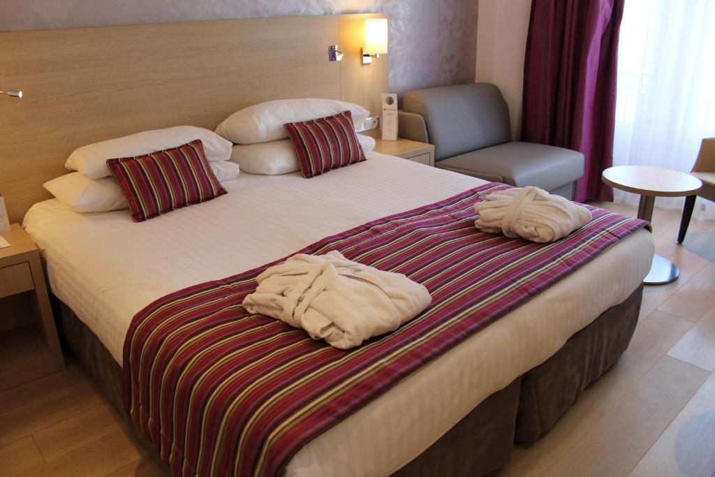 A bed or beds in a room at Best Western Plus Hotel Carlton Annecy
