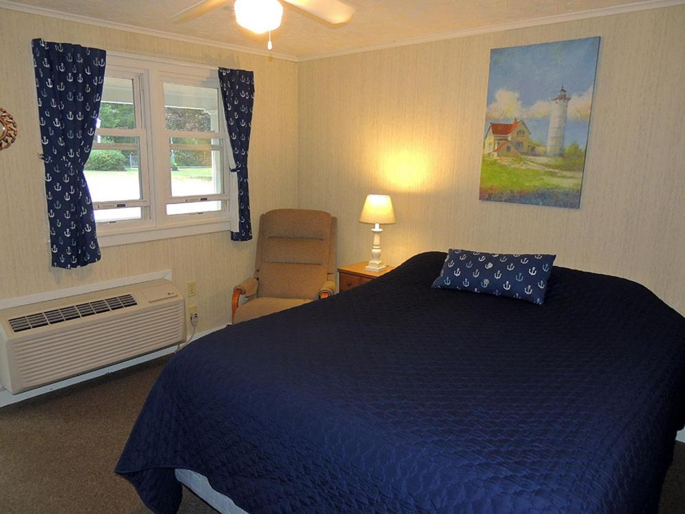 A bed or beds in a room at West Winds Motel & Cottages
