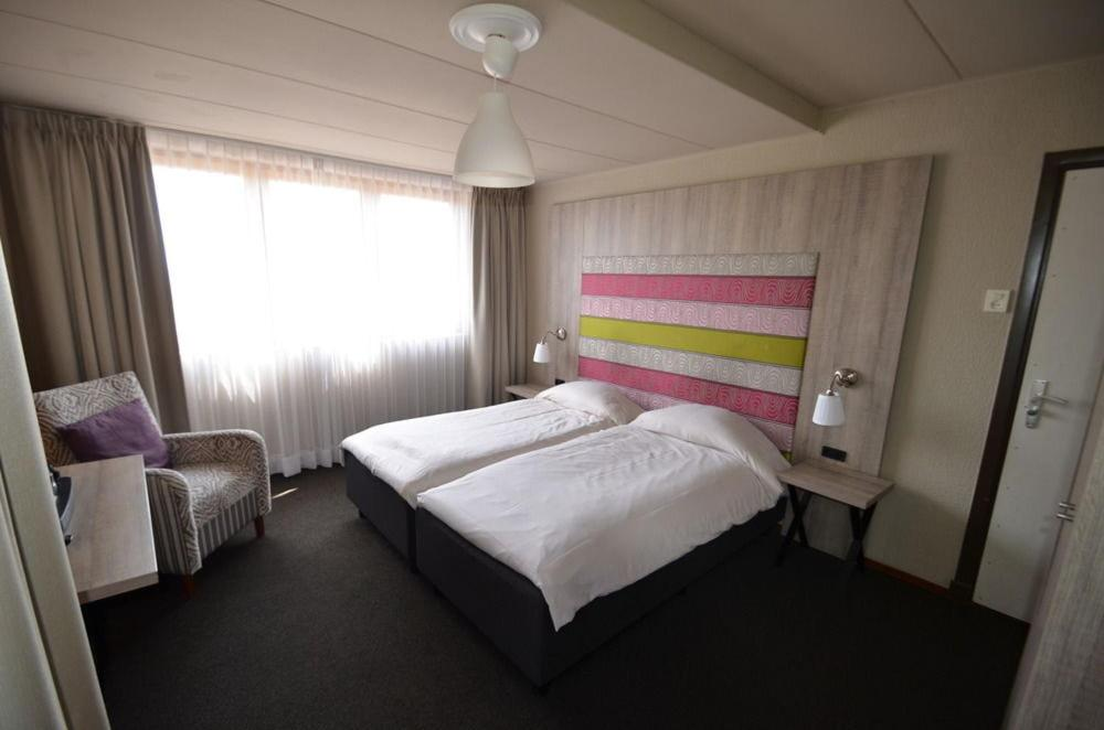 A bed or beds in a room at Herberg 't Voshoes