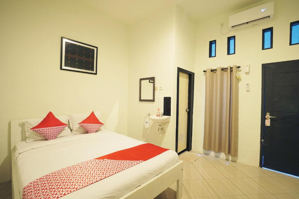 A bed or beds in a room at OYO 967 Cajoma Guesthouse