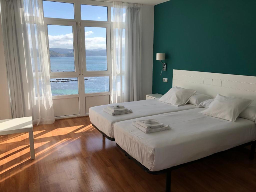 A bed or beds in a room at Hotel Mar de Fisterra