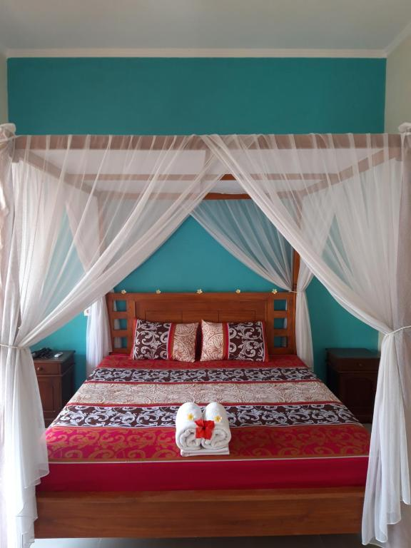 A bed or beds in a room at Bumbung Bungalows