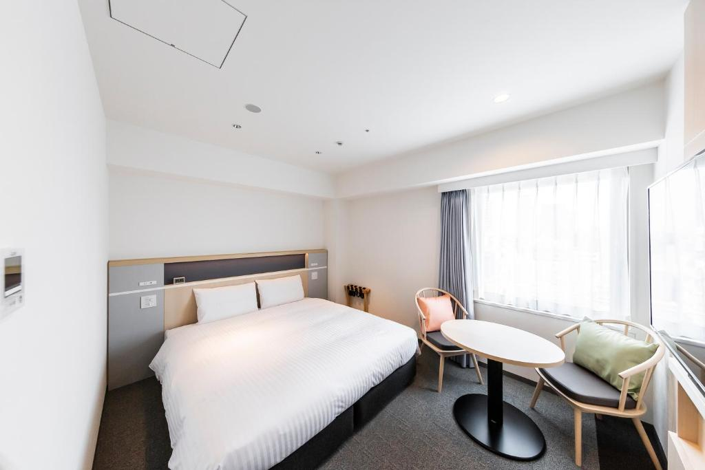 A bed or beds in a room at Via Inn Shinsaibashi Yotsubashi