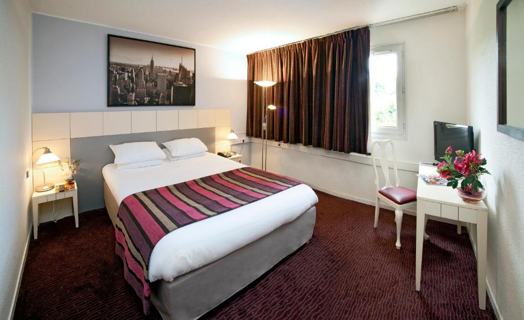 A bed or beds in a room at Hotel The Originals Boutique Rosny Golf