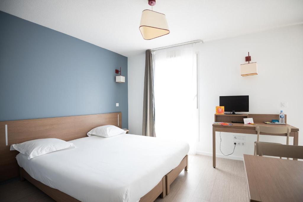 A bed or beds in a room at Zenitude Hôtel-Résidences Narbonne Centre