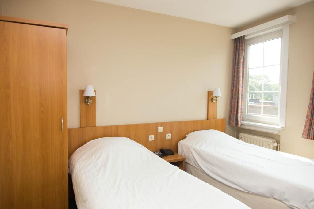 A bed or beds in a room at Hotel Bristol Internationaal