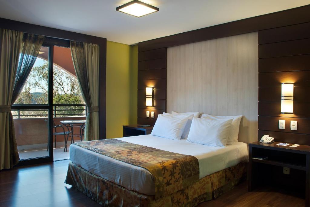 A bed or beds in a room at Master Gramado Hotel - A 1 quadra da Borges de Medeiros