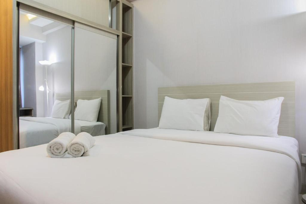 A bed or beds in a room at Simply Studio Apartment @ Grand Dhika City By Travelio