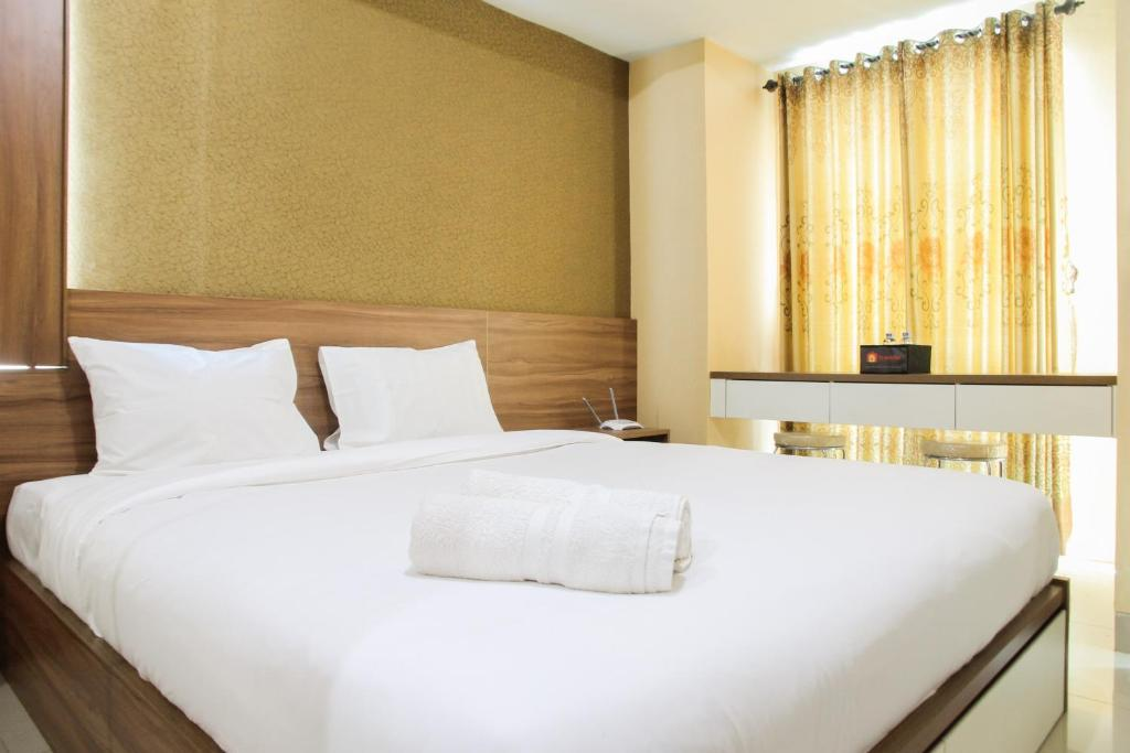 A bed or beds in a room at Relaxing Studio @ Grand Dhika City Apartment By Travelio