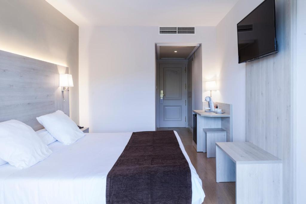 Een bed of bedden in een kamer bij Hotel Helios Lloret