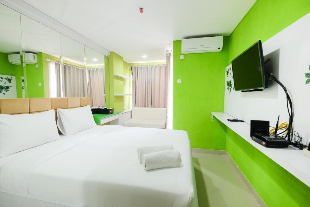 A television and/or entertainment center at Best Price Studio @ The Enviro Apartment By Travelio
