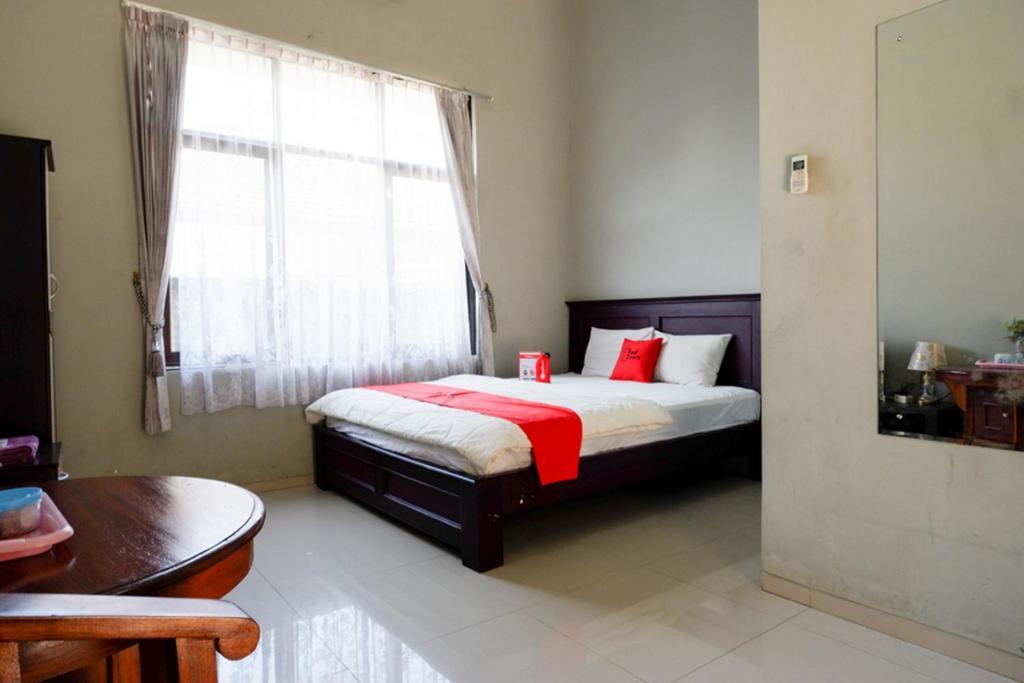 A bed or beds in a room at RedDoorz Syariah near Menara Kudus