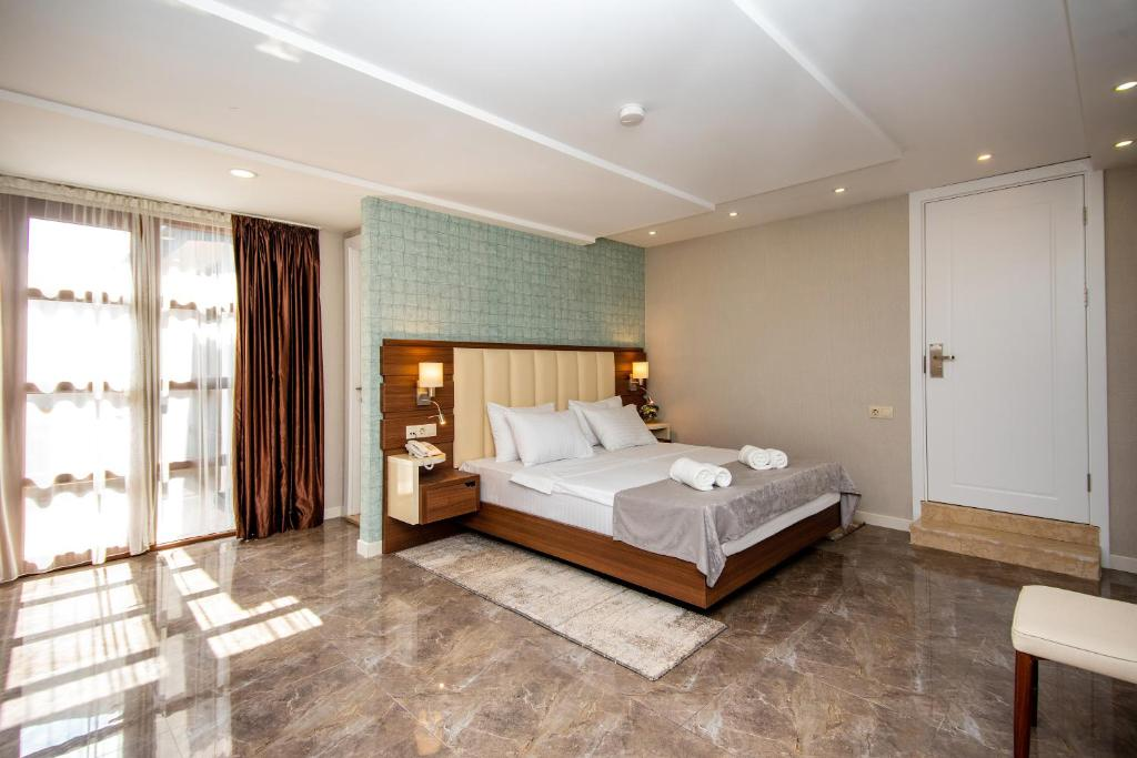A bed or beds in a room at Margi Boutique Hotel