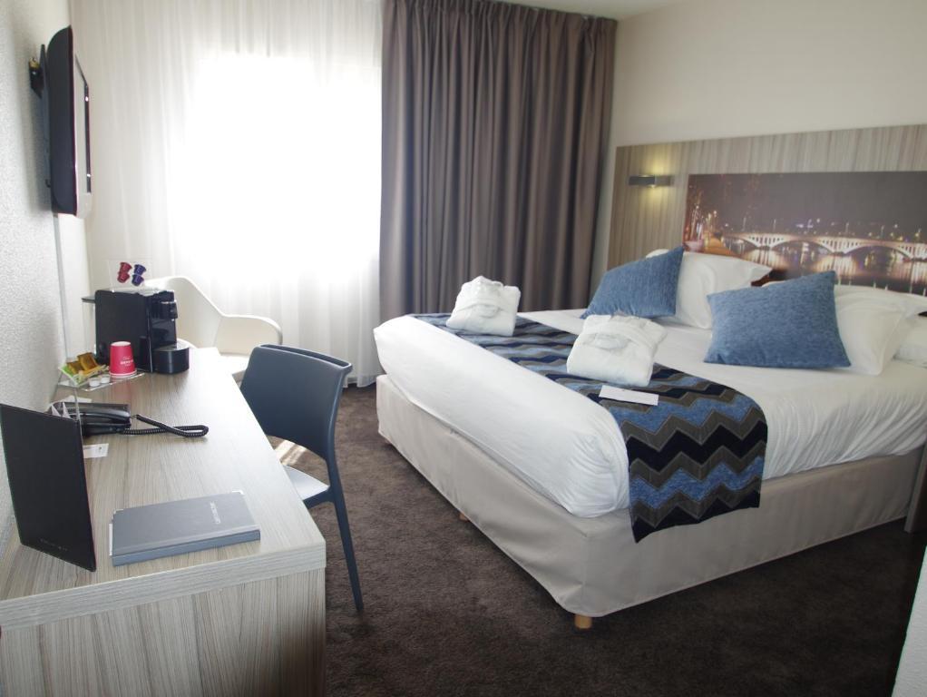 A bed or beds in a room at Hôtel Saphir Lyon